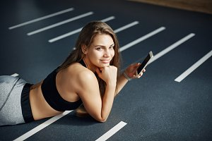 Portrait of beautiful woman laying in gym after a hard training using a smart phone to post photos to social media.