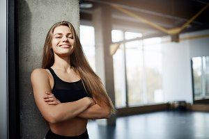 Portrait of adult fitness coach lady looking at camera with empty gym on background. Fit body concept.
