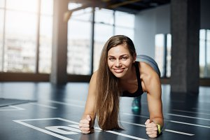 Portrait of adult beautiful woman doing elbow plank exercise on a gym floor. Healthy fitness body concept.