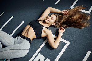 Portrait of young fitness lady with long hair having a rest after exercises in gym. Looking at camera smiling. Healthy body concept.