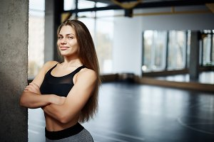 Portrait of beautiful fitness coach woman with long hair and a smile in gym space. Hard work and dedication is the path to perfect body. Healthy life concept.