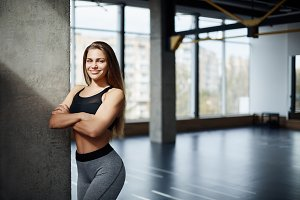 Portrait of beautiful adult fitness trainer stranding in gym. Posh woman did her job to get a perfect body shape and lose excess weight. Healthy life concept.