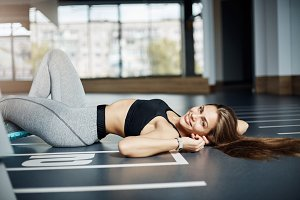 Young fit woman with perfect body taking a break from exercises to regain stamina. Healthy fitness concept.