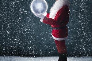 Santa holding glowing planet earth