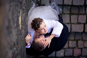Bride strokes groom`s head while