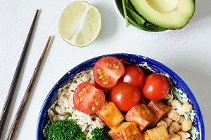 Healthy vegetarian salad bowl with tofu, broccoli, rice and avocado on white background