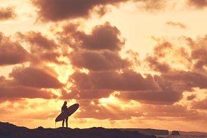 Surfer girl silhouette on sunset
