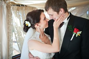 A bride strokes groom`s face