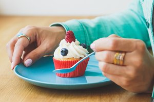 Woman's hands with cupcake on the plate