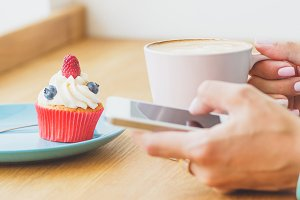 Cupcake with raspberry and blueberry on the plate, cup of cappuccino and woman's hand with a phone