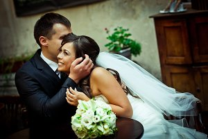 Handsome groom kisses bride`s