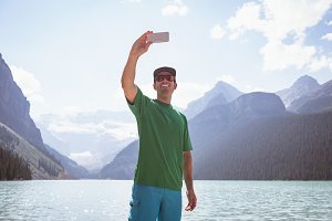 Happy man taking selfie near lake