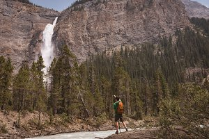 Male hiker taking picture of waterfall with mobile phone