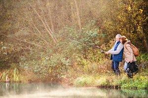 Senior couple fishing at the lake in autumn.