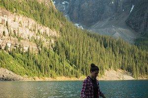 Woman walking on driftwood near lake