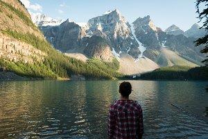 Rear view of woman standing near lake