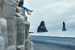 woman posing sitting on basalt columns at Black Beach in Iceland