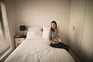 Pregnant woman sitting on the bed