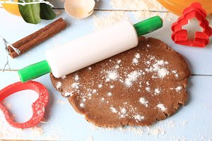 rolled out dough for gingerbread Christmas homemade cakes on a light wooden background selective soft focus rustic style