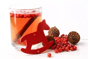 Christmas tea with cranberry Christmas decorations cones grog cider winter white wooden background rustic