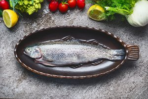 Raw whole trout fish in baking dish