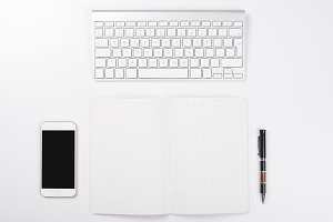 Smartphone, computer keyboard next to open notebook and a ballpoint pen on white background. Isolated.