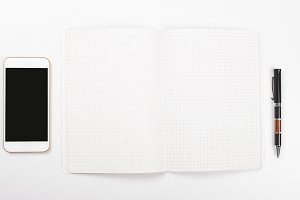 Smartphone next to open notebook and a ballpoint pen on white background. Isolated.