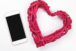 Smartphone next to red heart on white background. Isolated.