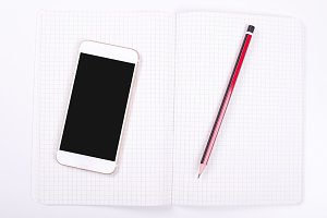 Smartphone next to notebook and pen on white background. Isolated.