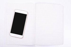 Top view of smartphone next to notebook on white background. Isolated.