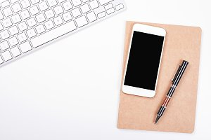Top view of smartphone and computer keyboard next to notebook and pen on white background. Isolated.