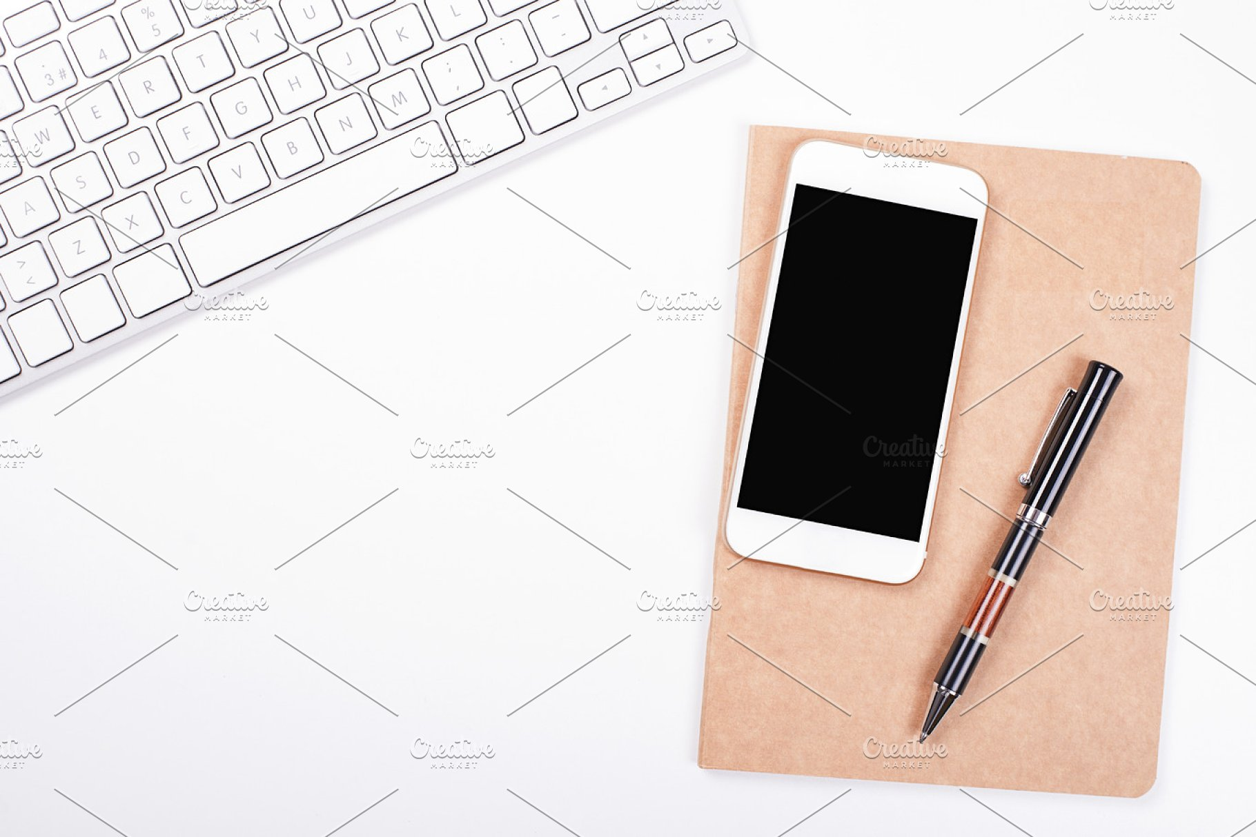 Top view of smartphone and computer keyboard next to notebook and pen on  white background  Isolated