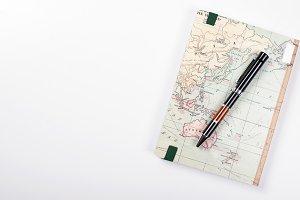 Vista superior de una libreta de viaje y un bolígrafo sobre fondo blanco. Aislado.