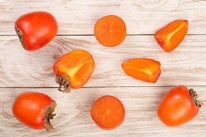 persimmon on white wooden background. Top view. Flat lay pattern