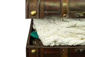 chest with knitted woolen winter clothes retro vintage