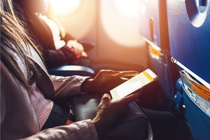 Close-up image of female hands holding smartphone sitting in the airplane