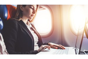Woman working using laptop while travelling by plane