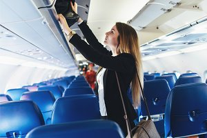 Female student putting her hand luggage into overhead locker on airplane