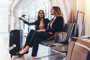 Two business ladies waiting for the flight in airport international terminal