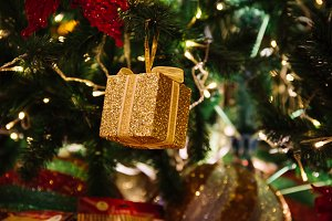 Beautiful decorated Christmas tree background with gold gift box and xmas ornaments