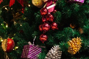 Beautiful decorated Christmas tree background with pine nuts under Christmas tree and xmas ornaments hanging on the tree
