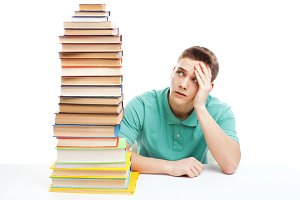student at the desk with books stack