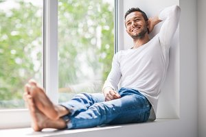 man sitting on window sill