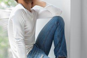man sitting on window sill