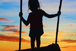 Child on sea beach swing