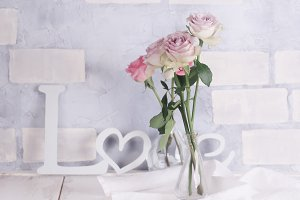 delicate roses on a brick background with the word love
