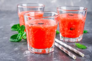 Watermelon smoothies in glasses with mint leaves on a gray dark concrete background.