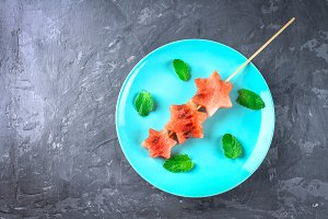 Watermelon in the form of stars on skewers with leaves of mint lies on a blue plate. Top view.