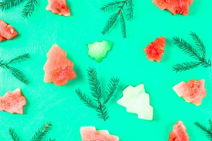 Watermelon in the form of Christmas trees with spruce branches on a green background. Flat lay. Top view.