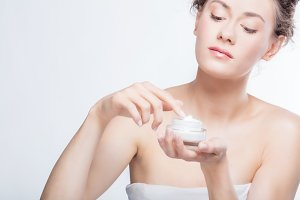 Young, attractive woman using a face cream.